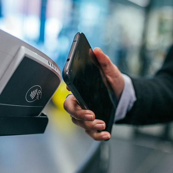 person scanning their phone next to a tap-to-pay terminal