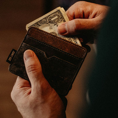 man holding wallet with cash in it