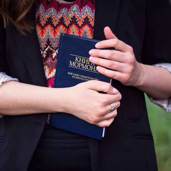 young woman holding a copy of the Book of Mormon in a foreign language