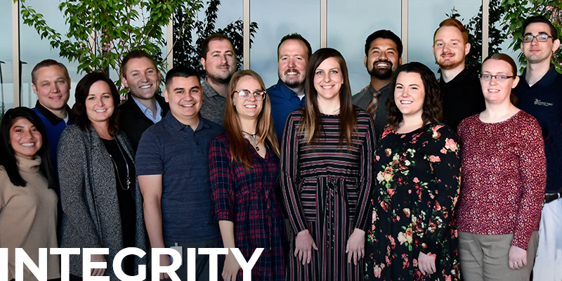 group of DFCU employees smiling, with text overlay: Integrity